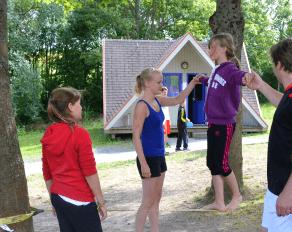 Trainer helfen Teilnehmerin beim Slacklining