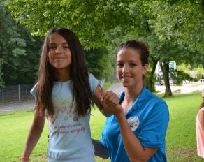 Trainerin hilft Teilnehmer auf Slackline